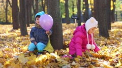 Two children sits near tree in autumn park with dry leaves Stock Footage