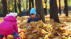 Little boy sits near tree and girl throws leaves in autumn park Stock Footage