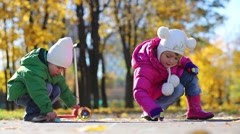 Girl and boy draw by chalk on asphalt in autumn park Stock Footage