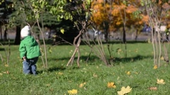 Little girl and boy run and jump on grass in autumn park Stock Footage