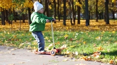 Little boy rides scooter in autumn park with dry leaves Stock Footage