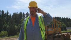 Blue collar worker walking and talking on phone - stock footage