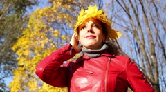 Woman in red with crown made of maple yellow leaves smiles Stock Footage