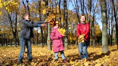 Mother and two children throw yellow fallen leaves in autumn park Stock Footage