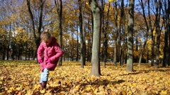 Little girl in pink dances in autumn park with fallen foliage Stock Footage