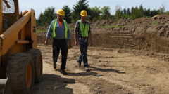 Construction workers walking and talking on job site - stock footage