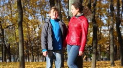 Mother and happy son talk in autumn park with fallen foliage Stock Footage