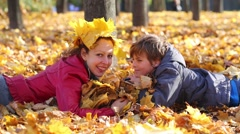 Smiling mother and son lie on yellow leaves in autumn park Stock Footage