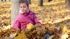 Pretty girl in pink sits near tree and throw leaves in park Stock Footage