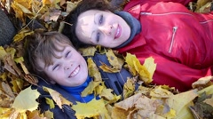 Mother and her son lie on many yellow fallen leaves in park Stock Footage