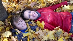 Mother and her son lie on leaves and daughter lies on mother Stock Footage
