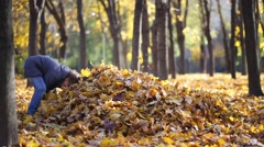 Mother and two children make big heap of yellow fallen leaves Stock Footage