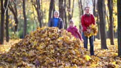 Mother and two children make big heap of fallen leaves together Stock Footage
