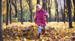 Girl jumps above heap of leaves and legs of boy stick out Stock Footage