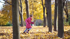 Girl in pink runs and jumps to big heap of yellow fallen leaves Stock Footage