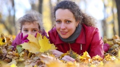 Mother and daughter lie on yellow fallen leaves in autumn park Stock Footage