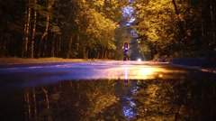 Woman rides bicycle with lights in park at summer evening Stock Footage