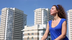 Pretty woman in blue sunbathe near new buildings at sunny day Stock Footage