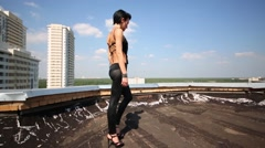 Woman goes and dances on roof at background of buildings Stock Footage
