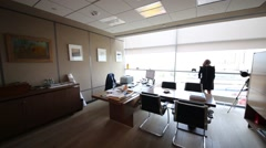 Stock Video Footage of Back of woman looking to window in office with tables and closet