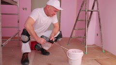 Master mixes pink paint before fixing on wallpaper Stock Footage