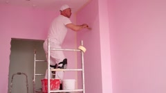 Builder with brush in hand painted walls in pink room Stock Footage