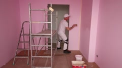 Plasterer in white clothes and kneepads works in new room - stock footage