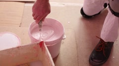 Hand of colourer mixes paint before fixing on wall Stock Footage