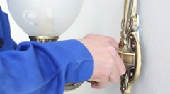 Hands of worker in blue setting sconces on pink wall in new room Stock Footage