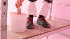 Feet of colourer with brush working in new pink room Stock Footage