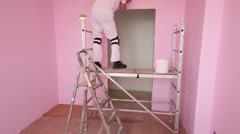 Man in white with brush works on scaffolding in pink room Stock Footage