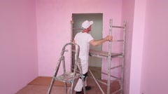 Man in white moves scaffolding in pink new room before work Stock Footage