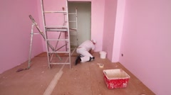 Finisher with brush on floor paints wall in new pink room Stock Footage