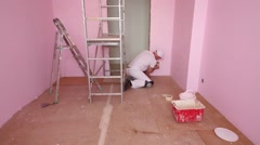 Worker in cap and white clothes paints wall in pink room Stock Footage