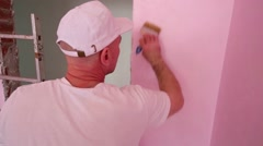 Worker in cap and white clothes paints wall in new room Stock Footage