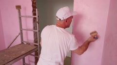 Worker in cap and white clothes paints wall in room Stock Footage