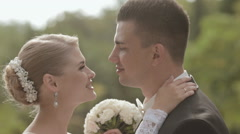 Beautiful bride and groom kissing and cuddling on the nature - stock footage
