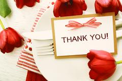 Dinner table setting with Thank You card and tulips Stock Photos