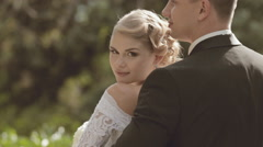The groom embraces fiancee standing in a park Stock Footage