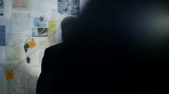 4K Police detectives working together in incident room to try and solve a case - stock footage