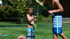 Two young boys having squirt gun fight in slow motion,  Shot with a Phantom - stock footage