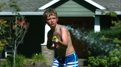 Two young boys having squirt gun fight in slow motion,  Shot with a Phantom Stock Footage