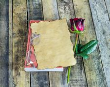 Fresh red rose,glasses and old paper on notebook on a wooden background - stock photo
