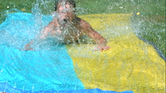 Young boy on water slide in slow motion,  Shot with a Phantom Camera at 1000 Stock Footage