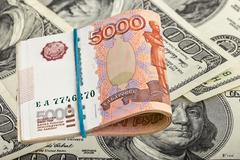 Russian rubles on dollars background - stock photo