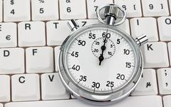 Stopwatch on computer keyboard Stock Photos