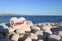 "Stock Photo of ""Amour"" written on heart shaped stone on the beach"