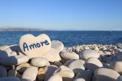 """""""Amore"""" written on heart shaped stone on the beach Stock Photos"""