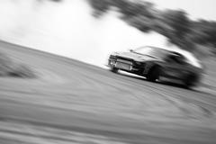 Stock Photo of Very fast driving, motion blur drift black and white