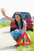 woman with a warning triangle in case of breakdown - stock photo